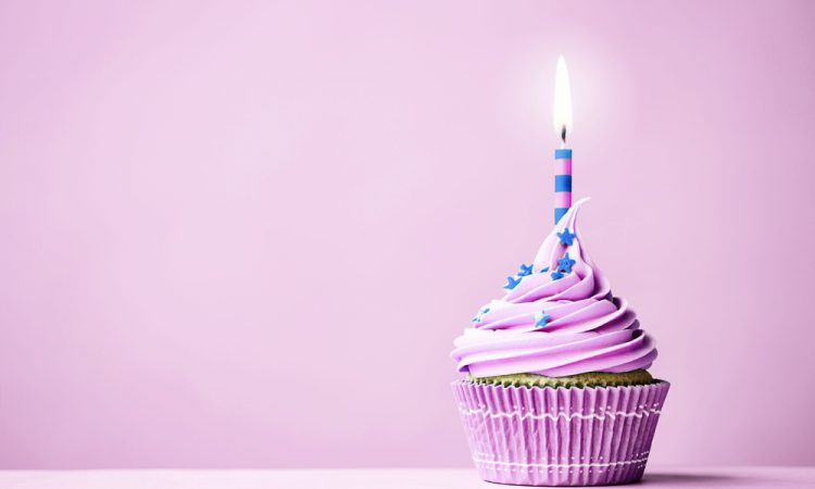Purple birthday cupcake with copy space to side