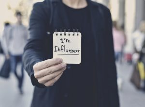 closeup of a young caucasian man in the street showing a spiral notepad with the text I am influencer written in it