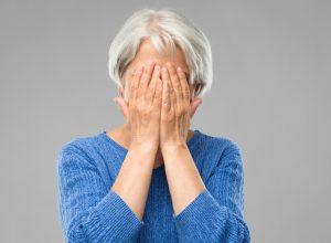 stress, emotions and old people concept - sad senior woman covering her face by hands over grey background