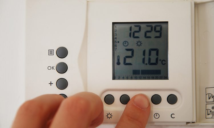 hand setting the temperature of the heating thermostat