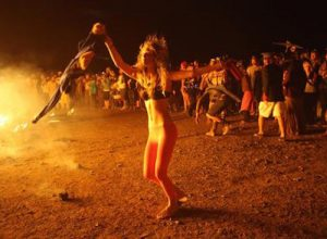 epa03200035 A girl dances around the remains of the main effegy after it was burt on the last night of the 'AfrikaBurn' festival in the the Karoo desert, Tweefontein, South Africa, late 28 April 2012. The festival is based on the well known 'Burning Man' festival in the United States and sees thousands of people gathering in the desert to construct a temporary community. The event is part rave, part trance party, part Pagan gathering, part arts festival as thousands of participants erect art pieces, share ideas, share goods and gifts and burn the effigies on the final night. There must be no trace of humans after the event is finished and a sharing community is formed as there is no money allowed as participants have to bring their own food, water and tents.  EPA/KIM LUDBROOK